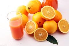 Glass krus av ny orange fruktsaft med nya frukter på den vita tabellen Arkivbilder