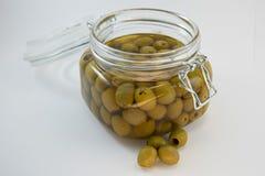 Glass krus av oliv på vit bakgrund Royaltyfri Foto