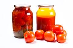 Glass krus av på burk tomater och tomatfruktsaft på vit backgr Royaltyfri Bild