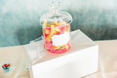 Glass krus för färgad godis på den söta stångtabellen royaltyfri fotografi