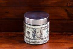 Glass krus med dollarräkningar Arkivfoto