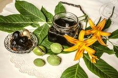 Glass krus med driftstopp av gröna tokiga och orange liljor på tabellen Arkivfoto