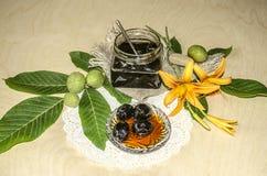 Glass krus med driftstopp från valnötter på valnötsidor och orange liljor Arkivfoto