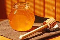Glass krus med honung- och träpinnen Royaltyfria Foton