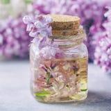 Glass krus med olje- arom och med lila blommor för brunnsort och aromatherapy Tvål-, handduk- och blommasnowdrops royaltyfria bilder