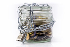 Glass krus med pengar och den låsta kedjan Royaltyfri Foto