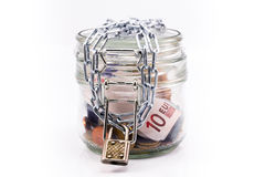 Glass krus med pengar och låst kedja Royaltyfri Fotografi
