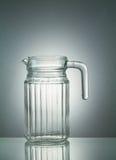 Glass krus med reflexion på upplyst vit bakgrund Fotografering för Bildbyråer