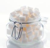 Glass krus mycket av kuber för vitt socker Arkivbilder