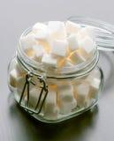 Glass krus mycket av kuber för vitt socker Royaltyfri Foto