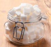 Glass krus mycket av kuber för vitt socker Royaltyfria Foton
