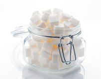 Glass krus mycket av kuber för vitt socker Royaltyfria Bilder
