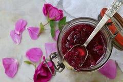 Glass krus och liten sked med rosa kronbladdriftstopp för te på ljus marmorbakgrund Kopiera utrymme för text Arkivfoton