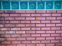 Glass kvarter på bakgrunden för vägg för röd tegelsten Fyrkantigt glass block Royaltyfri Fotografi