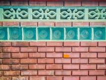 Glass kvarter på bakgrunden för vägg för röd tegelsten Fyrkantigt glass block Arkivfoton