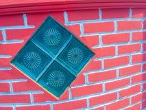 Glass kvarter på bakgrunden för vägg för röd tegelsten Fyrkantigt glass block Arkivbild