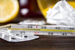 Glass kvicksilvertermometer med en hög temperatur av 37 5 mot bakgrunden av mediciner, citron, te, folk boter, minnestavlor, Royaltyfri Foto
