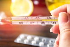 Glass kvicksilvertermometer med en hög temperatur av 37 5 mot bakgrunden av mediciner, citron, te, folk boter, minnestavlor, Arkivbild