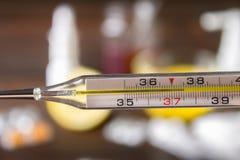 Glass kvicksilvertermometer med en hög temperatur av 37 5 mot bakgrunden av mediciner, citron, te, folk boter, minnestavlor, Arkivfoton