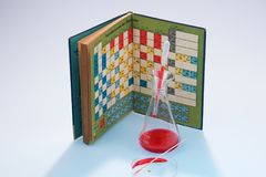 Glass laboratory apparatus with chemicals and book. With periodic table Stock Photo
