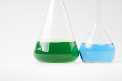 Glass laboratory apparatus with green and blue water. Isolated Stock Images