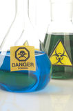 Glass laboratory equipment with symbol biohazard and danger Royalty Free Stock Photos