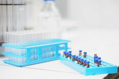 Glass laboratory tubes, vials and test tubes for collecting samples and conducting tests close-up on a special plastic rack. royalty free stock photography