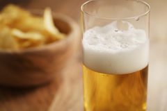 Glass of lager beer with potato chips on wooden table Royalty Free Stock Images