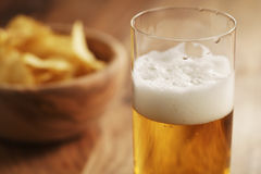 Glass of lager beer with potato chips on wooden table Royalty Free Stock Photo