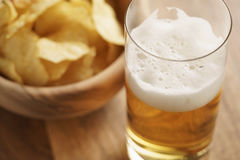 Glass of lager beer with potato chips on wooden table Royalty Free Stock Photos