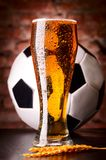 Glass of lager on table with soccer ball stock image