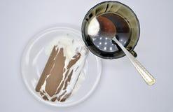 Glass Lakomka i smältt choklad på en vit platta- och kaffekopp med skeden med servetten som isoleras på vit bakgrund Arkivfoto