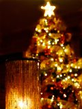 A glass lamp with a candle with a blurred lighted christmas tree in the dark royalty free stock photography