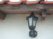 Glass lampa på väggen under taklutningen Arkivfoto