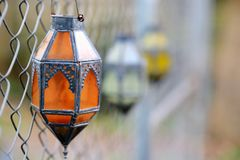 Glass Lanterns hanging on chain link fence Royalty Free Stock Image