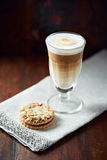 Glass of latte coffee and almond cookies Stock Photos