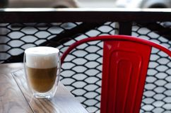 A glass of latte coffee is on the cafe table. Near the red iron chair royalty free stock photo