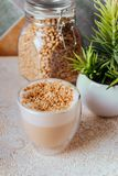 Glass of latte coffee on light table. With almond nuts stock images