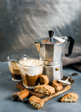 Glass of latte coffee on rustic wooden board, cantucci biscuits and steel Italian Moka pot, grey background Stock Images