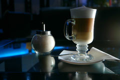 Glass of latte coffee shugar and spoon on glass table. Stock Photo