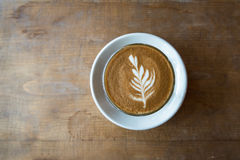Glass of latte coffee on wooden table. In coffee shop royalty free stock photo