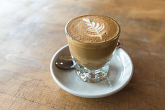 Glass of latte coffee on wooden table. In coffee shop stock photography