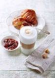 Glass of Latte Macchiato and Croissant with Rhubarb Jam Stock Photo
