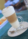 Glass of Latte Macchiato. With spoon on the plate on a  table Royalty Free Stock Photo