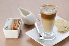 A glass of latte. Serve with biscuit stock image