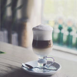 Glass of latte on the table in cafe Royalty Free Stock Photos