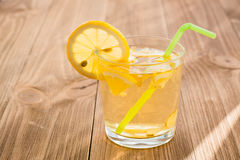 A glass with a lemon-ginger cool drink on a wooden table Royalty Free Stock Images