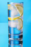 Glass of lemon ice water on blue background Stock Image
