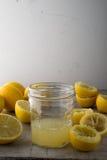 A Glass of Lemon Juice Alongside Fresh Lemons Stock Photography