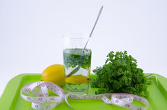 Glass of lemon and parsley on a green tray Royalty Free Stock Image